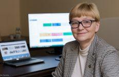 Dr Anida Stanik-Besler, prorektor ds. kształcenia i dydaktyki Politechniki Opolskiej. Za jej plecami widoczne są dwa monitory komputeró. Pani prorektor patrzy w obiektyw aparatu i lekko się uśmiecha.