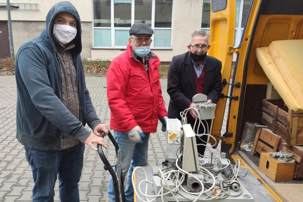 Trzech mężczyzn pakuje eksponaty muzealne do samochodu