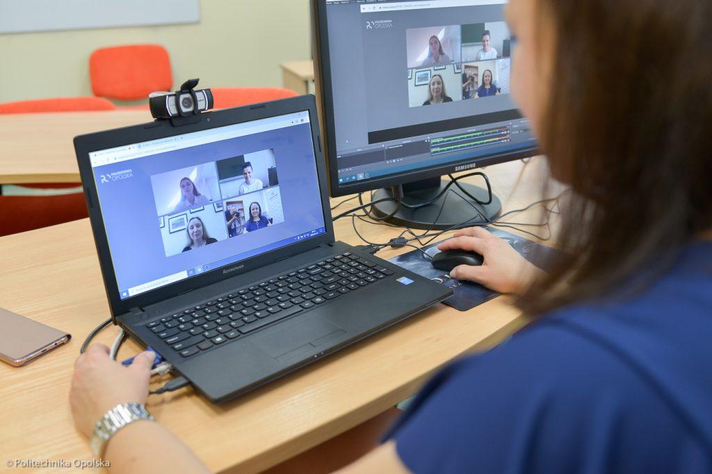 Osoba siedząca przed monitorami dwóch komputerów prowadzi rozmowę online. Twarz osoby nie jest widoczna, na monitorach widać natomiast twarze jej rozmówców.